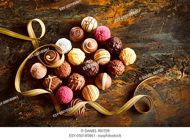Elegant display of luxury chocolate pralines arranged in a neat rectangle with swirling gold ribbon on rustic wood viewed from overhead