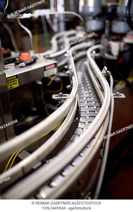 Curved assembly line conveyor belt for bottling beer in a brewery plant in Toronto Canada