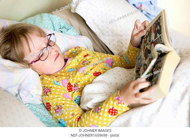 Girl lying in bed and reading comic book