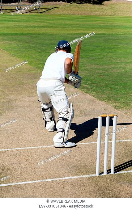 Rear view of cricket player practicing on field