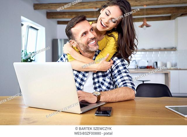 Happy couple sitting at dining table, embracing, using laptop
