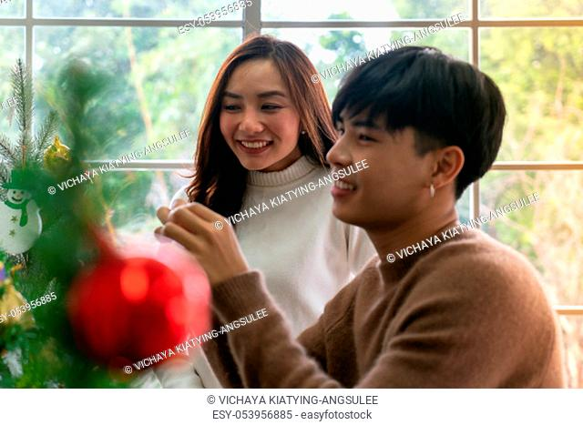Young Teenager asian couple decorating Christmas tree together prepare for Christmas party holiday