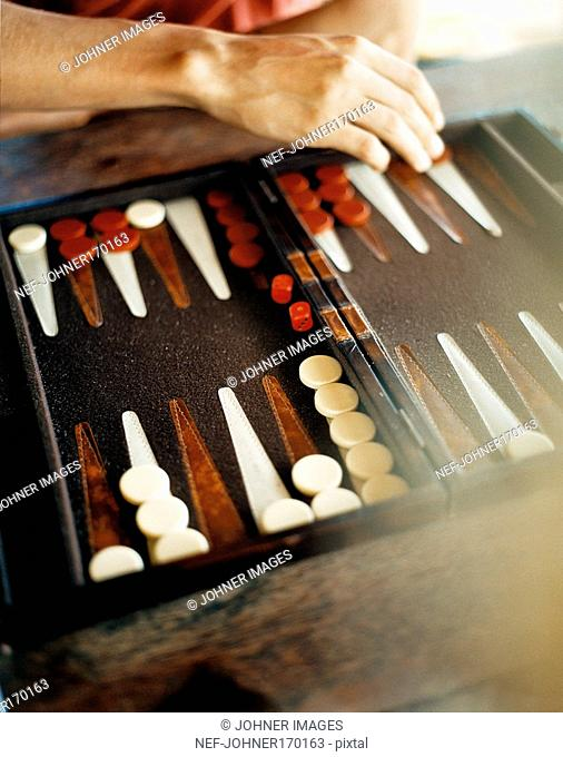 A hand moving a piece on a backgammon game