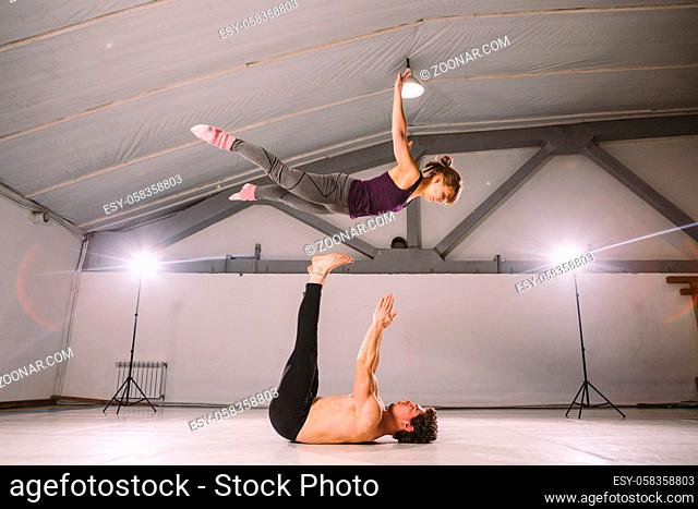 The theme of Acroyoga and Yoga Poses. Acroyogis practicing. with studio Backlight. the Base man tosses the Pops woman Flyer in flight up