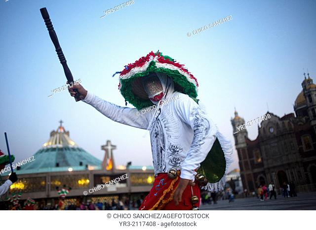 A dancer from Chocaman, Veracruz, wearing a shirt with the image of Our Lady of Guadalupe and holding a club, dances the Danza de los Santiagos at the...