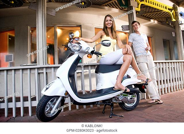 Portrait of young woman sitting on moped with boyfriend standing beside