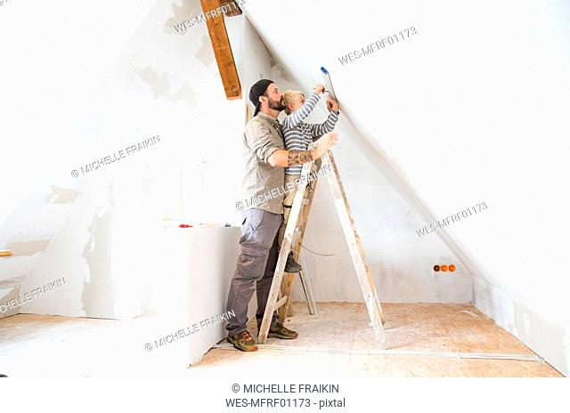 Father and son working on loft conversion using water level