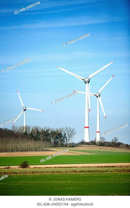 Illustration shows wind turbines in a Belgian field with blue sky