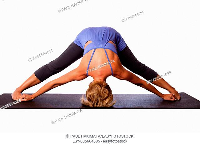 Beautiful healthy woman doing inversion Standing Intense Spread Leg Prasarita Padottanasana yoga pose with head on floor, on white