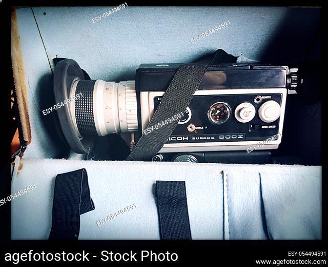 Fragment of vintage amateur film movie camera and reels of color motion picture films Super 8mm format close-up at selective focus
