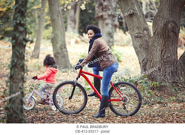 Mother and daughter bike riding in autumn woods