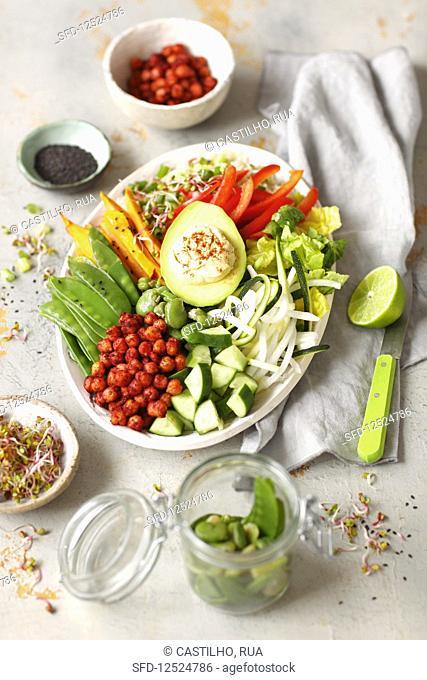 Vegan Buddha bowl with hummus, avo, sweet potatoes, baked chickpeas and vegetables