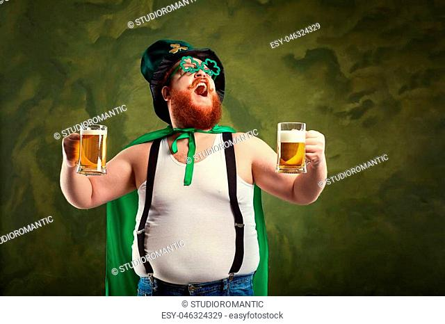 A fat man with a beard in St. Patrick's suit is smiling with a mug of beer on a green background