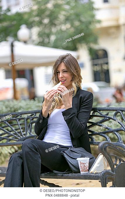 Executive woman ejoying her break with sandwich and coffee