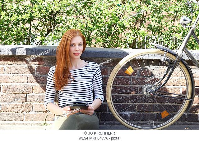 Portrait of redheaded woman with tablet and bicycle sitting on a wall