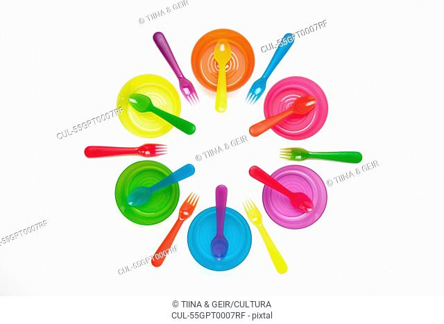 Colourful plastic plates, cups, bowls, spoons and forks