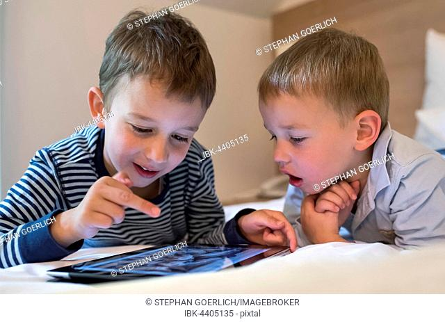 Two boys, siblings lying on a bed and playing with an iPad, Tablet PC