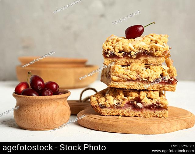 stack of baked crumble pie with fruit filling and sprinkled with grated almonds on a wooden board, gray background