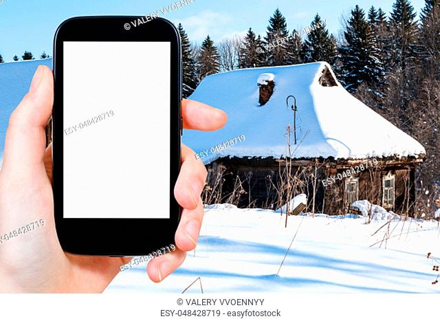 travel concept - tourist photographs of snow-covered old rural houses at the edge of forest in winter in Smolensk region of Russia on smartphone with cut out...