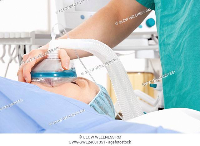 Anesthetist using an oxygen mask on a patient in a hospital