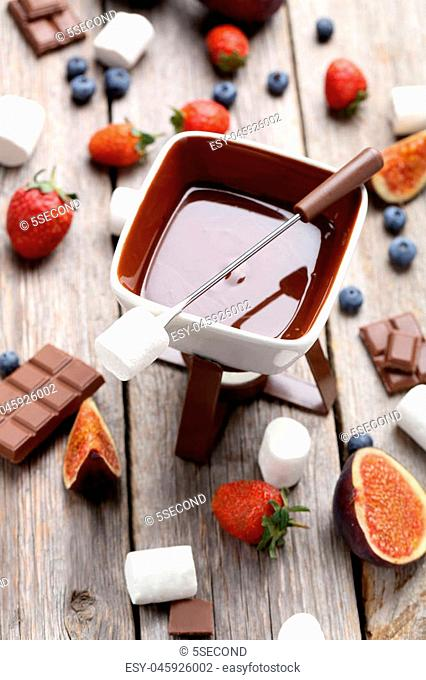 Chocolate fondue with fresh berries on a grey wooden table