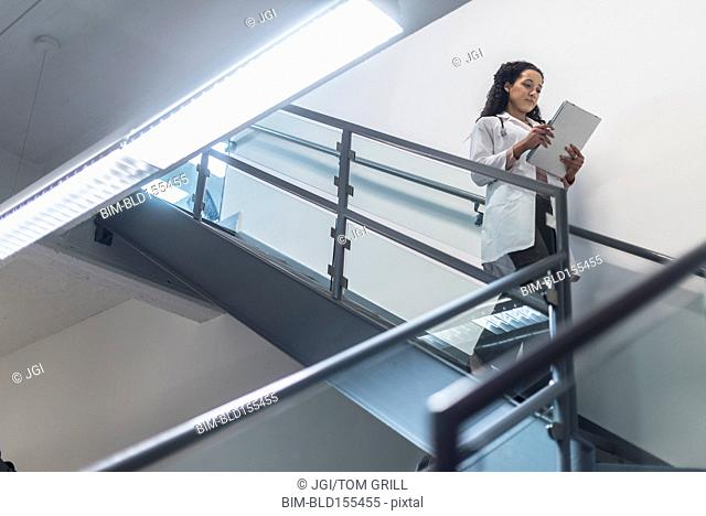 Low angle view of mixed race doctor reading medical chart on staircase