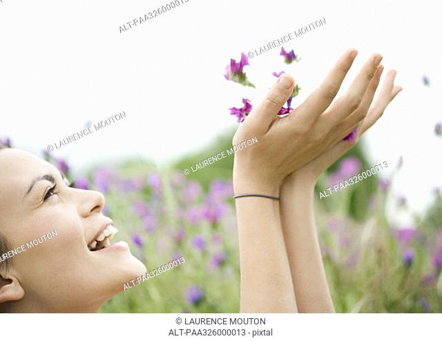 Young woman holding up flowers