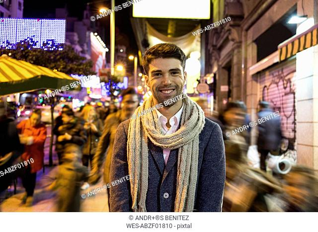 Portrait of smiling man in the city with unfocused people at night