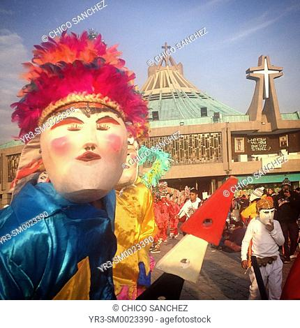Men wearing masks and dressed in bright colors dance in front of the basilica during the annual pilgrimage to the Our Lady of Guadalupe basilica in Mexico City