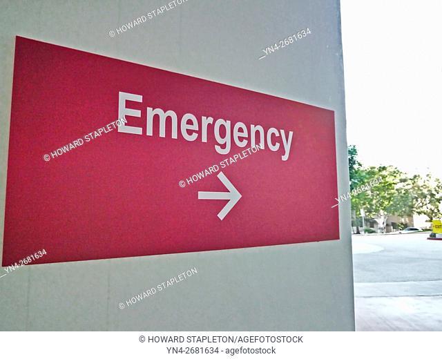 Hospital sign pointing toward the Emergency entrance
