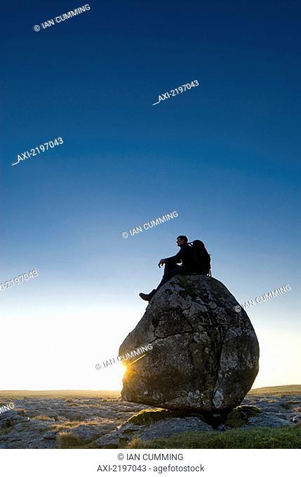 Man Sitting On Head-Shaped Boulder At Dusk, Twisleton Scars, Near Ingleton, Yorkshire Dales National Park, North Yorkshire, England