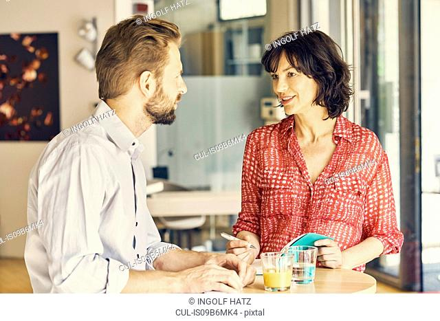 Businessman and businesswoman meeting in rest area
