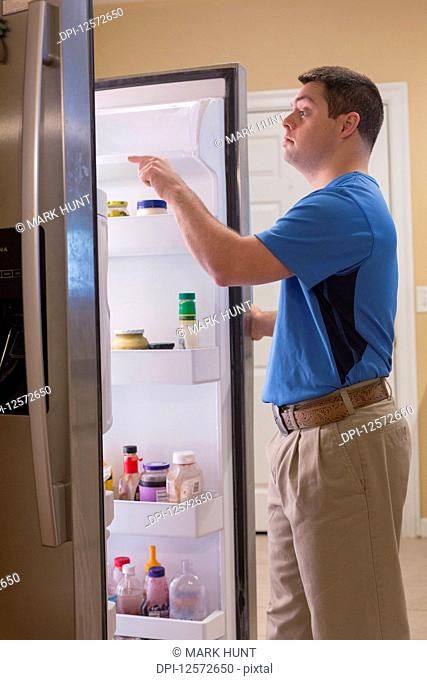 Man with Down Syndrome opening refrigerator in kitchen