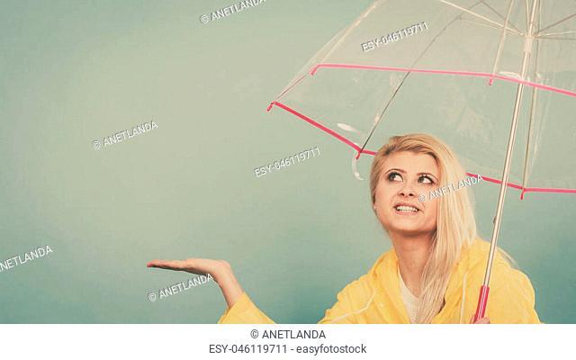 Blonde woman wearing yellow raincoat holding transparent umbrella checking weather if it is raining