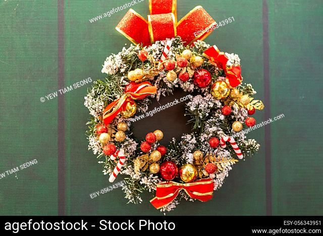 Christmas wreath decoration at green door background