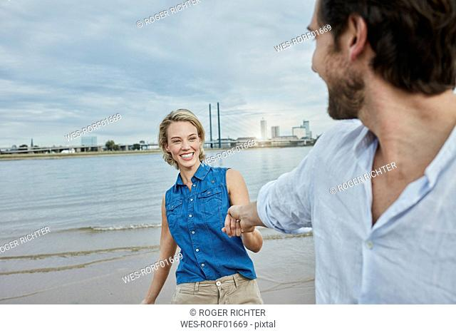 Germany, Duesseldorf, happy young couple at Rhine riverbank