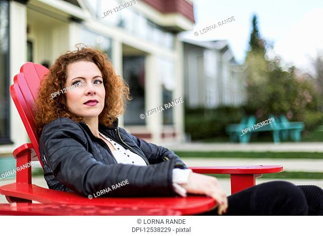 Portrait of a woman with red, curly hair sitting outdoors in springtime; North Vancouver, British Columbia, Canada