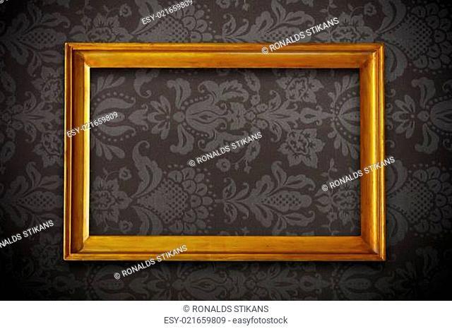 golden vintage empty frame on dark floral wallpaper