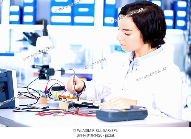 Female engineer soldering a circuit board