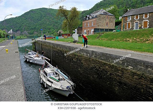 dismated sailing boat crossing the lock to the lateral canal of the Meuse River at Fumay, Ardennes department, Champagne-Ardenne region of northeasthern France