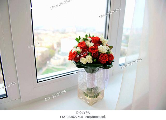 Wedding bouquet in a vase on a windowsill in the apartment on a high floor. View from above. View of the city