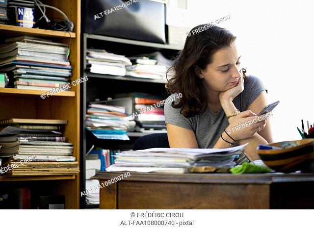 Office worker taking break to browse social media using smartphone