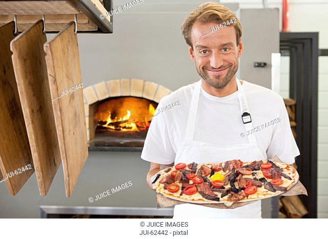 Smiling chef holding pizza in kitchen