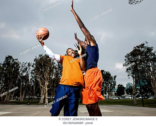 Young men playing basketball on court