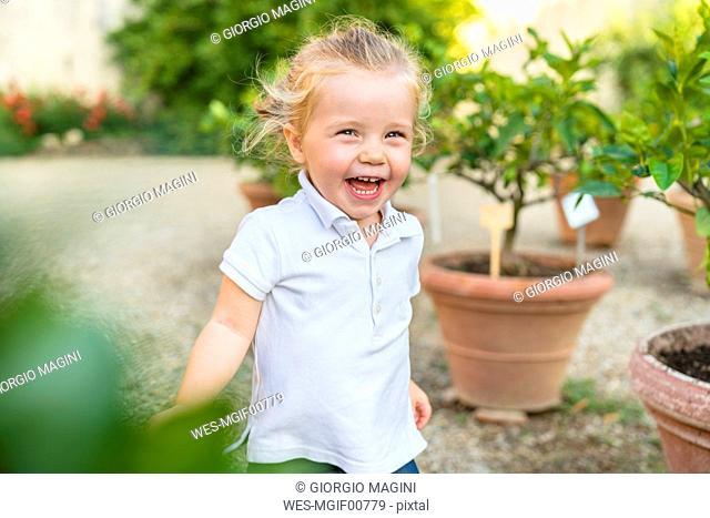 Happy little girl running along flower pots