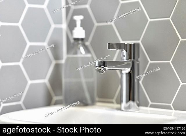 close up of water tap with liquid soap on sink
