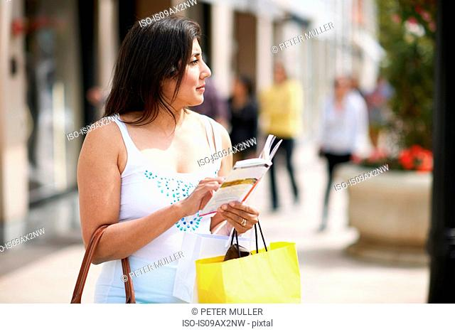 Woman with shopping bag and guide book