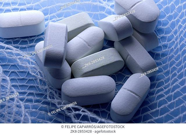 Some white pills wrapped in gauze on a blue background