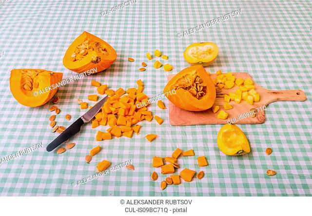 Pumpkin cut into pieces on chopping board with knife