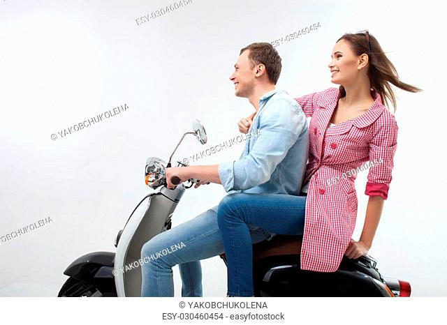 We are going in a new future. Cheerful loving couple is riding the scooter in the spring. They are sitting in profile and smiling. Isolated